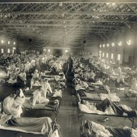 historic black and white photo of a large warehouse space filled with hospital beds, patients and providers