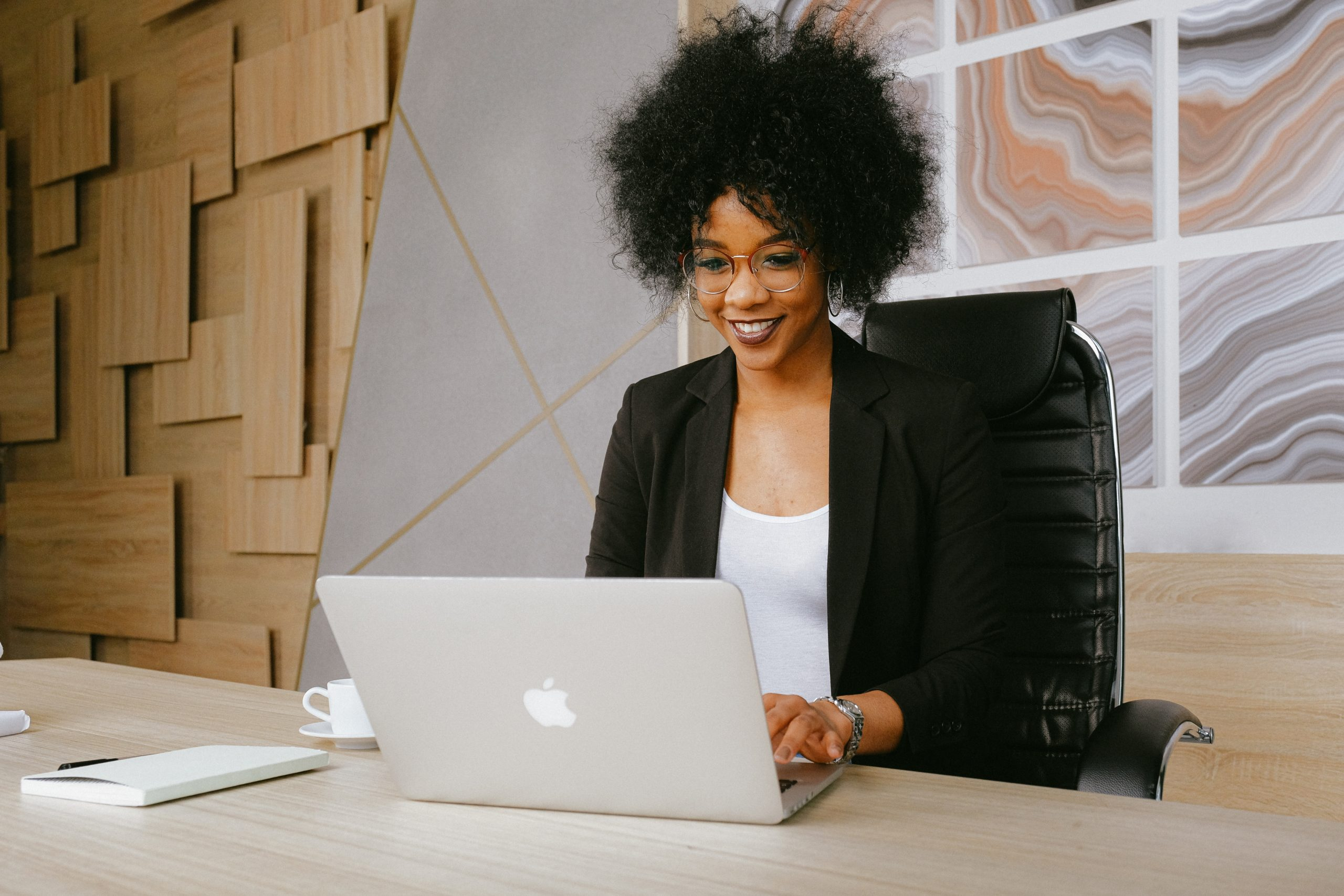 A Black female professional sits at a desk with a laptop computer
