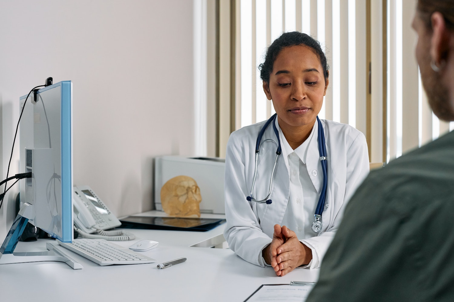 Female doctor sitting at her desk with a patient