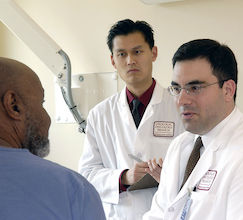 photo of two health care professionals talking to Black patient