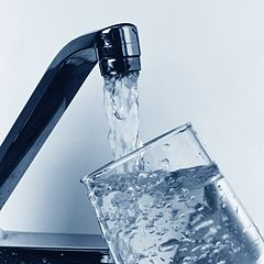water pouring from faucet into glass